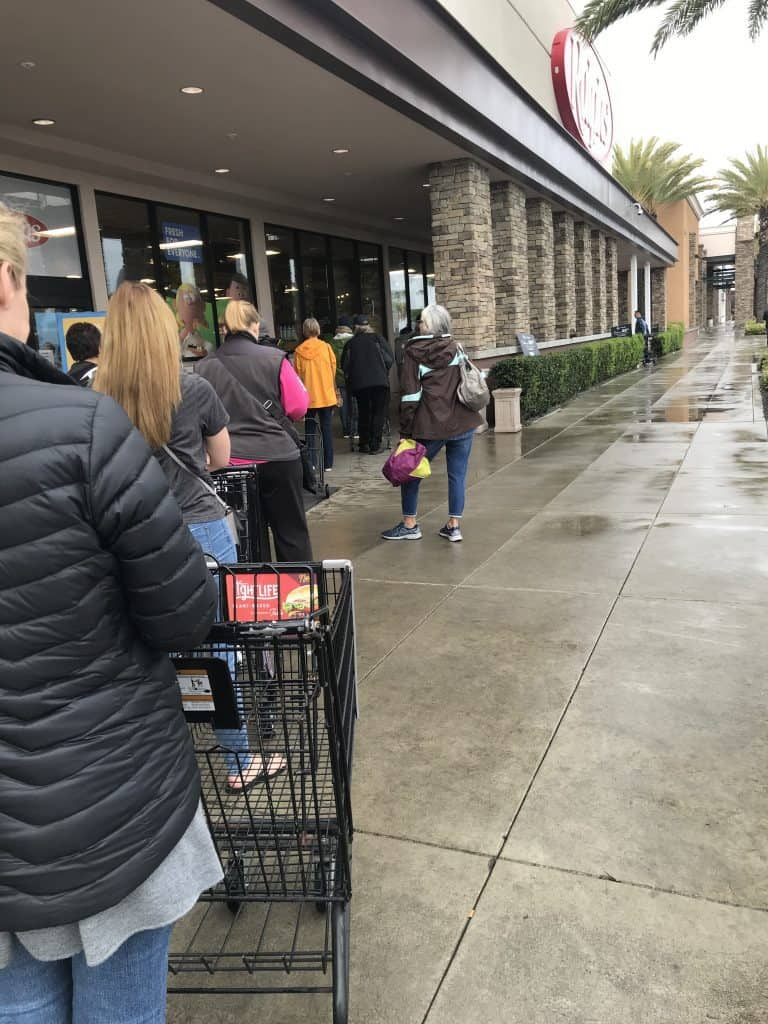 Standing in line awaiting entry to a grocery store.