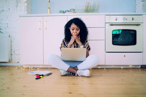 African American young adult showing anxiety while watching laptop - survive and thrive during COVID