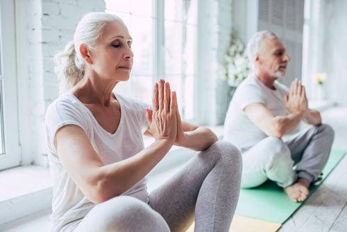 White elderly couple doing yoga
