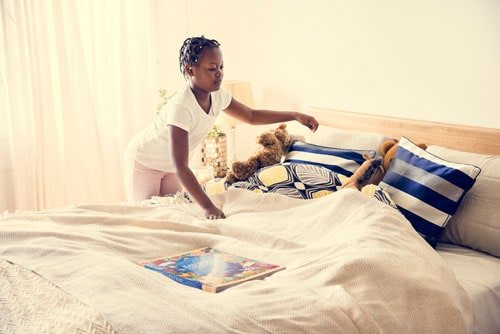 African American girl making her bed
