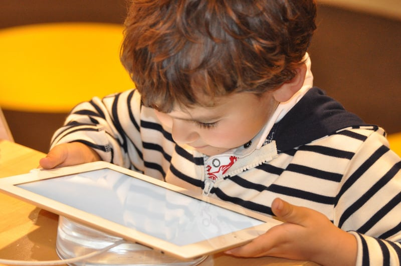 Photo by NadineDoerle--1421566 Litte boy reading a multicultural children's book on a tablet. Latinx