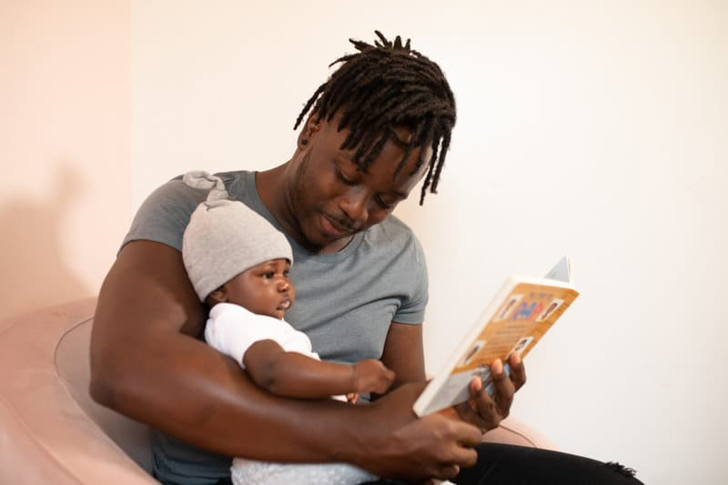 Photo by nappy.  Father reading a multicultural children's book to his baby.  African American