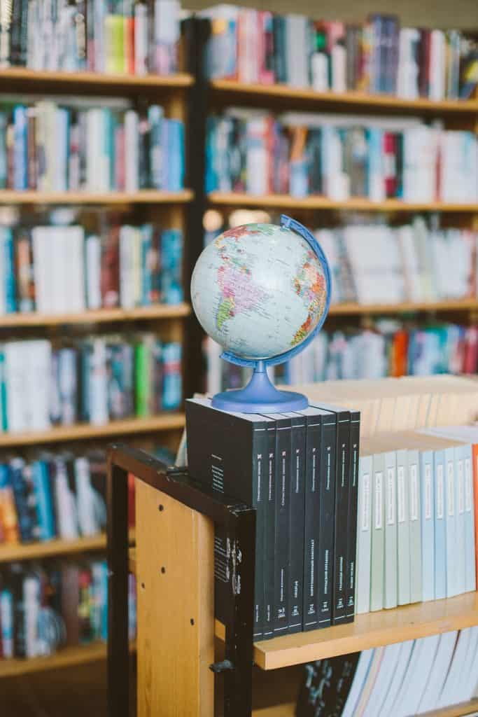 Photo by Polina Zimmerman. Reading the world. Books with extraordinary sense of place depicted with a globe and books.