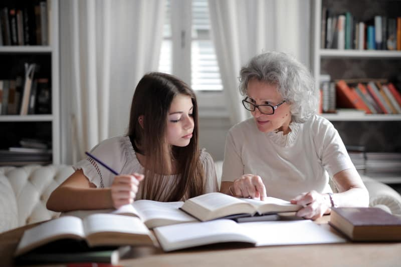 Photo by Andrea Piacquadio   Grandmother homeschooling girl at a table. Caucasian