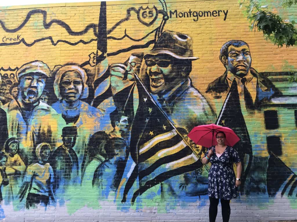 My daughter standing in front of a mural in Montgomery Alabama, an important site on the Civil Rights Trail, one of several road trip ideas.