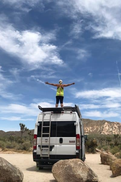 SSSNOO standing on top of van with arms spread