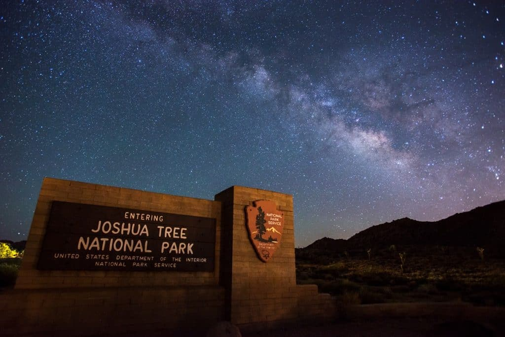 Night sky and Milky Way shown above Joshua Tree National Park entrance sign