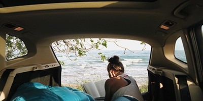 Woman in van reading a book set in California with beautiful landscape in background