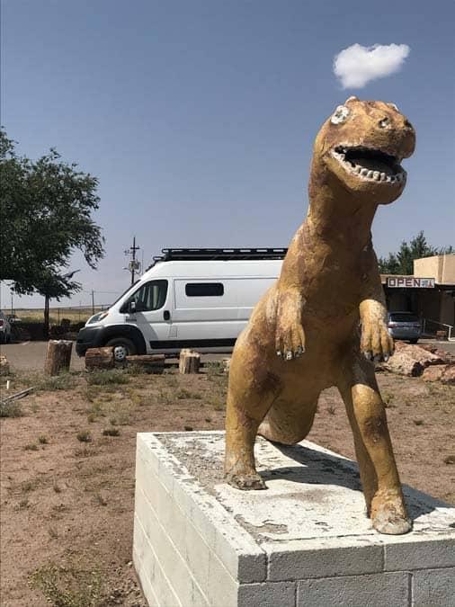 Promaster van behind dinosaur statue