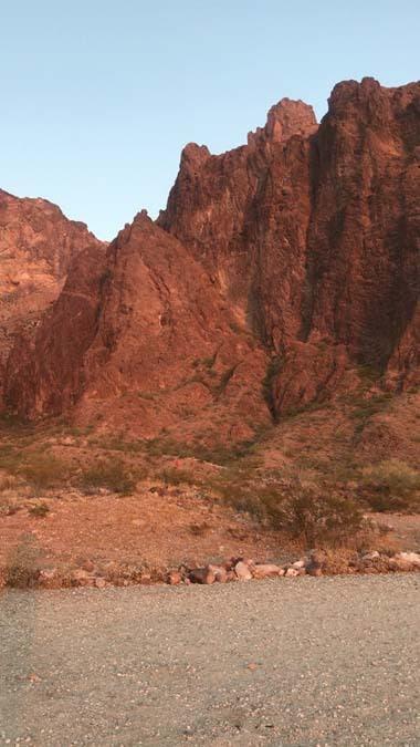 Kofa canyon walls turning a dark orange as the sun sets.