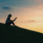 Sillhouette of seated woman reading a book with a sunset in the background.