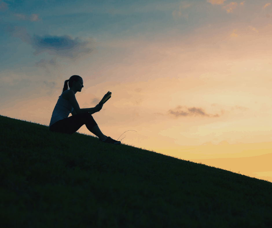Sillhouette of woman reading a book outdoors