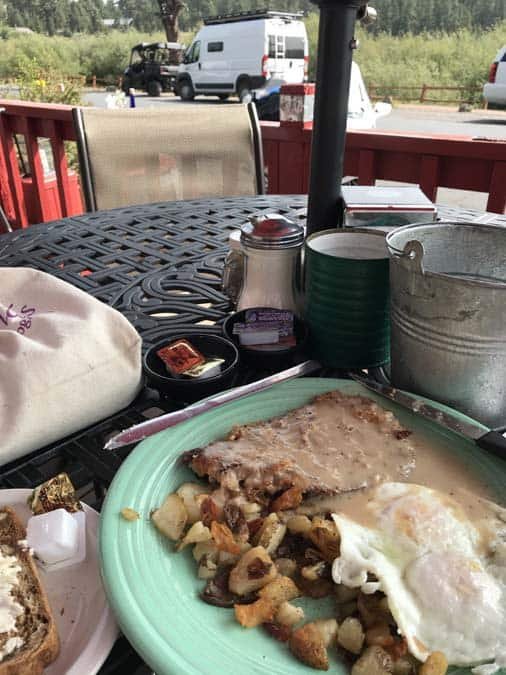 Rendezvous Cafe, Greer AZ. Outside table with breakfast.  Promaster campervan in the background.