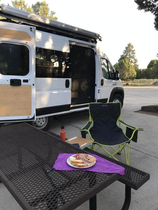Women camping alone in Fool Hollow Campground.  Show Low, AZ.  Spanish tapas dinner with a view.  converted Promaster van in background.